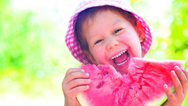 little girl eating a ripe juicy watermelon in summertime